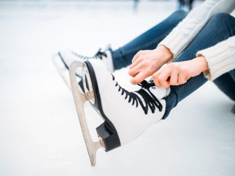 young-woman-ties-the-shoelaces-on-skates-P3A59QW